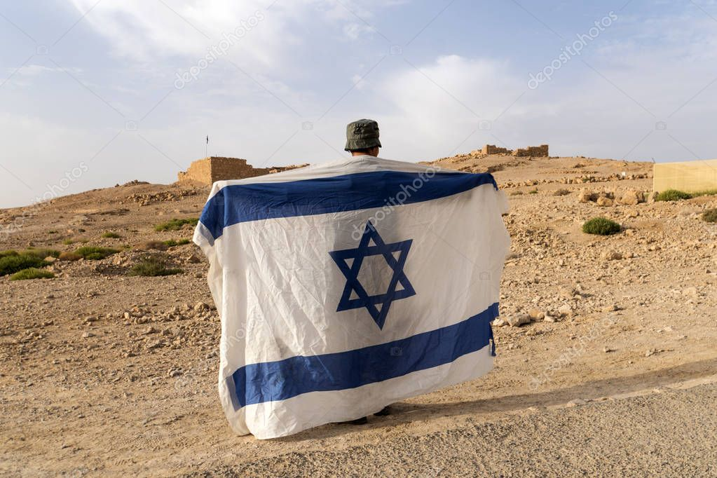 Back side of a soldier in hat holding the national flag of Israel - white with blue stripes and david's star at Masada fortification background. Young man sliping israeli flag over shoulders. Patriot