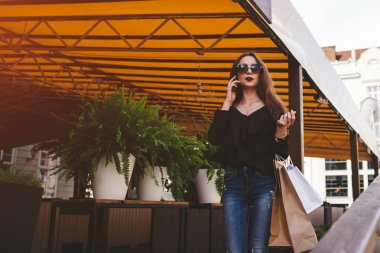 "Картина, постер, плакат, фотообои ""Beautiful stylish young woman with shopping bags walking out of cafe on city street and talking on phone. Fashion concept"", артикул 203737678"