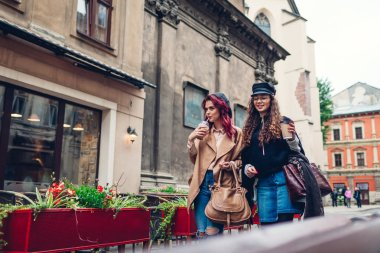 Outdoor shot of young women walking on city street. and having coffee. Happy friends talking and having fun