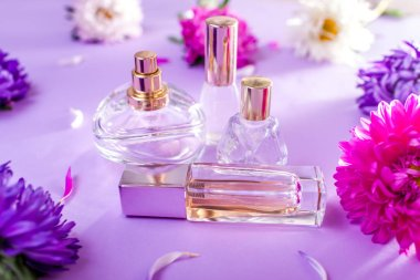 Bottles of perfume with purple and white flowers on violet background