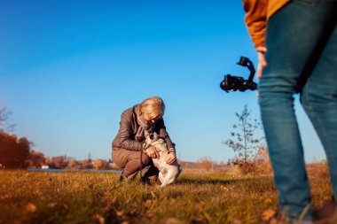 Videographer filming woman with dog in autumn park. Man using steadicam and camera to make footage. Video shoot. Stock filmmaker