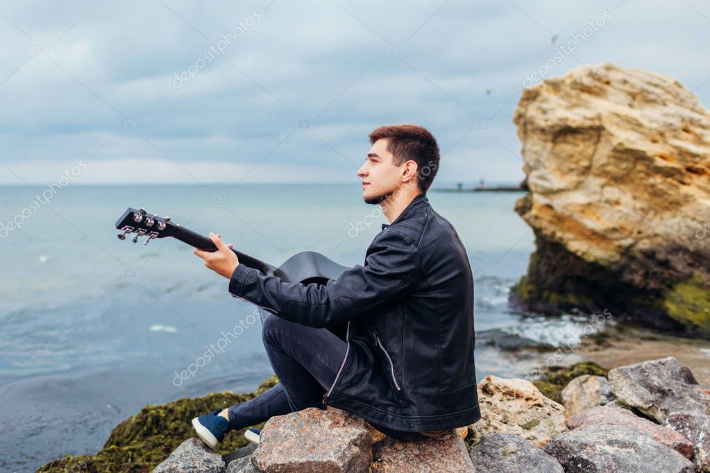 Young man with acoustic guitar playing alone on beach surrounded with rocks on rainy day