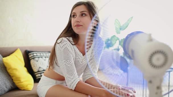 Fiatal nő lehűlése elektromos ventilátor otthon, míg az ivóvíz. Nyári hőség.