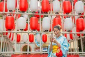Fotografia Asian woman using her cellphone in front of the lantern walls which is prepare for specific traditional festival.