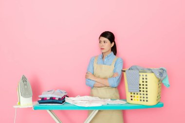 angry housewife unhappy to do housework standing behind ironing board