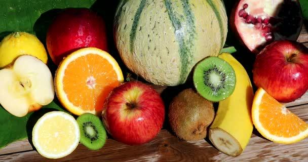 Víz fröccsenő over friss gyümölcsök. Több színes gyümölcsök: Apple, Orange, Kiwifruit, citrom, dinnye, gránátalma, banán és őszibarack. Közeli nézet-DCI 4k felbontás