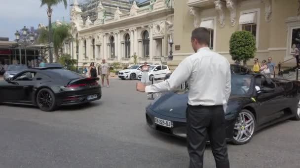 Monte-Carlo, Monaco - 16 giugno 2019: Giovane uomo alla guida di un lusso nero Ferrari F430 Spider di fronte al Casinò Monte-Carlo in Monaco Sulla Riviera Francese - 4k Video