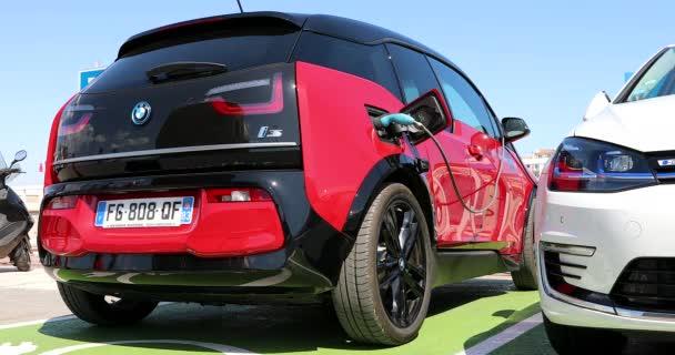 Saint-Tropez, Francie-7. září 2019: moderní černé a červené BMW i3 elektrické auto zaparkované na nabíjecí stanici v Saint Tropez na Francouzské riviéře, var, Francie, Evropa, zavřít pohled-DCI 4k video