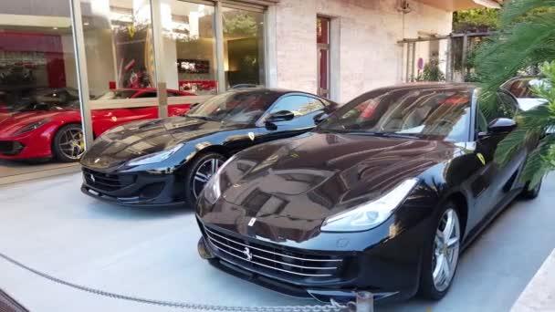 Monte-Carlo, Monako-20. září 2019: dva luxusní vozové vozy zaparkované před Scuderia Monte-Carlo, oficiální prodejce automobilů Ferrari, 5 Avenue Princesse Grace v Monaku na francouzském Riviera, Evropa-4k video