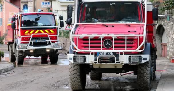 Breil-Sur-Roya, Frankreich - 8. Oktober 2020: Zwei rote Geländewagen der französischen Feuerwehr säubern die Straßen von Breil-Sur-Roya, einer Stadt, die während des Sturms Alex von der Überschwemmung des Flusses Roya überschwemmt wurde - DCi 4K Resolution