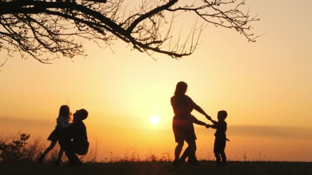 Silhouettes of happy family spending time together in the meadow near a big tree during sunset. Happy child rushes into hands of father. Dad throws his daughter up and catches her during sunset