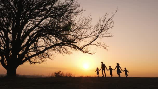 Silhouettes of family holding the hands and running in the meadow during sunset.