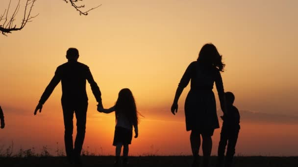Silhouettes of happy family holding the hands in the meadow during sunset. Happy family enjoying life together. Happy young family spending time together outside in green nature. Back view.