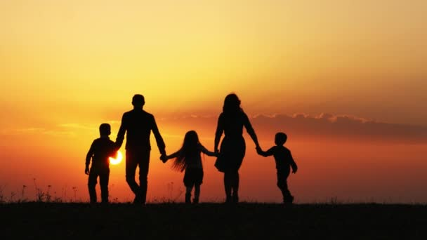 Silhouettes of happy family walking together in the meadow during sunset.