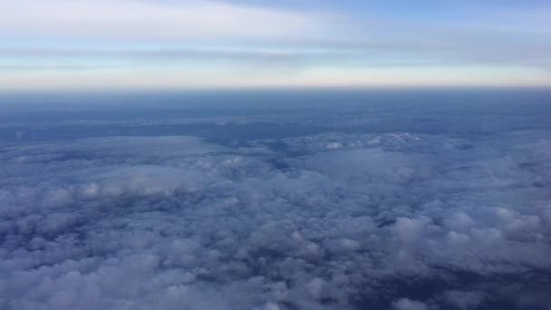 Amazing footage of aerial view above the clouds. Flying over the clouds. View from the airplane window to the blue sky and white clouds. Flying over beautiful sky and clouds.