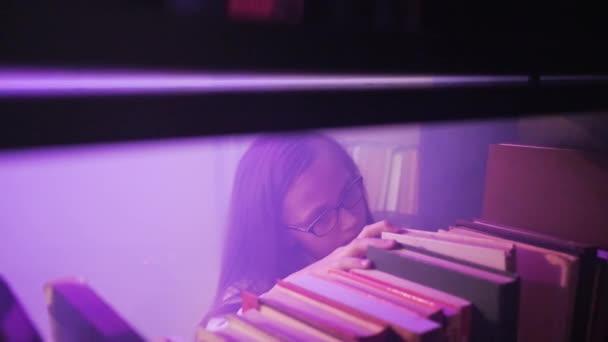 Dívka se probírá knihami na policích knihovny, magický kouř se točí kolem.