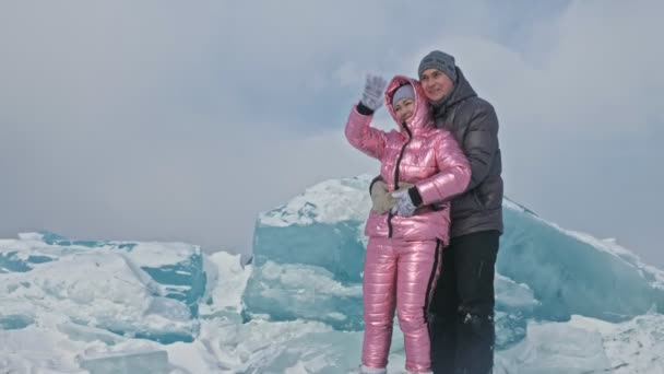 Young couple has fun during winter walk against background of ice of frozen lake. Lovers are having fun, laughing, jumping, kissing near a huge blue ice floe. Honeymoon. Love story.
