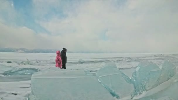 Young couple has fun during winter walk against background of ice of frozen lake. Lovers walk on ice, hold each other by hand, kiss and hug. Honeymoon. Love story.