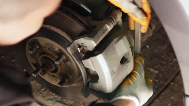 Auto mechanic working on brakes in a car repair shop domestic garage