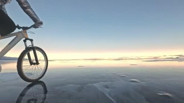 Frau fährt Fahrrad auf dem Eis. Bekleidet ist das Mädchen mit einer silberfarbenen Daunenjacke, einem Fahrradrucksack und einem Helm. Eis des zugefrorenen Baikalsees. die Reifen am Fahrrad sind mit speziellen Spikes überzogen.