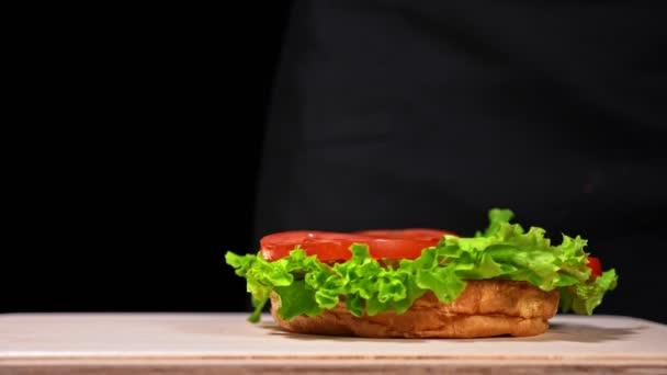 Burger főzés fekete alapon fekete élelmiszer kesztyű. Nagyon zamatos levegő zsemle és a márványos marha. Étterem, ahol minden hamburgert főtt kézzel. Nem készült ideális. Úgy néz ki, igazi, szerető kézzel készített.