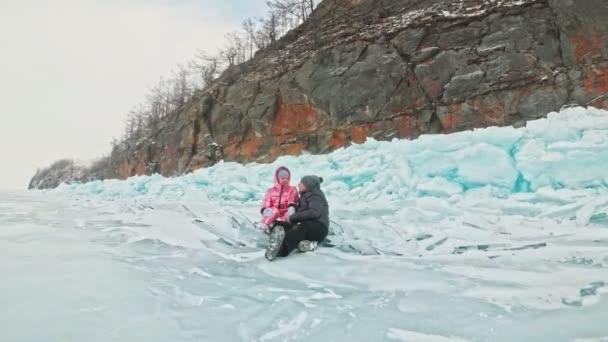 Mladý pár se baví v zimní procházka pozadí ledu zamrzlého jezera. Milenci sedí na ledu, polibek a objetí. Mladí šťastní lidé procházku sněhem pokryta ledem. Líbánky. Příběh lásky.