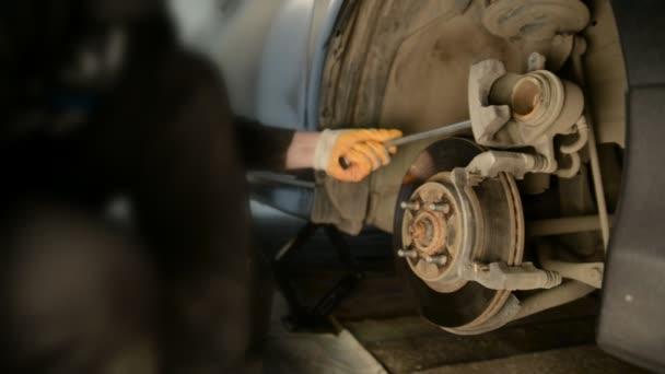Autószerelő dolgozik, fékek, autó javítás üzlet hazai garázs.