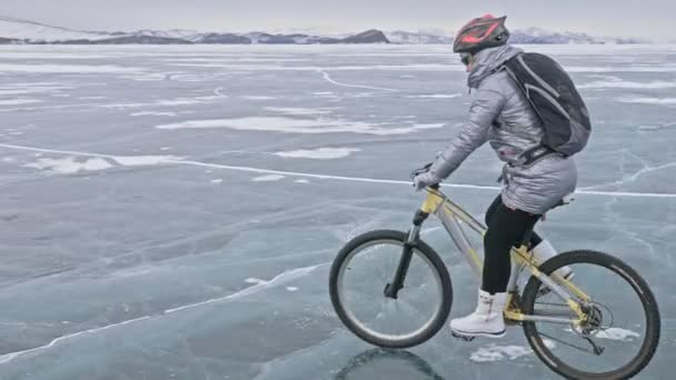 Žena je jízda kole na ledě. Dívka je oblečená v stříbřitě péřová bunda, Cyklistika helma a batoh. Ledem zamrzlé jezero Bajkal. Pneumatiky na kole jsou pokryty speciální hroty