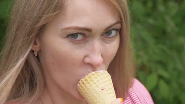 Žena olizuje zmrzlina. Dívka je lízání lahodný krém zmrzlinu. Kužel zmrzliny s jahodovou příchutí je její oblíbená letní jídlo. Západ slunce paprsky zářit v objektivu.