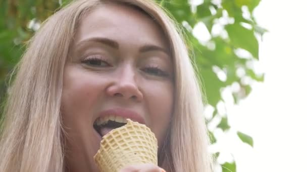 Woman licks ice cream. The girl is licking a delicious cream ice cream. Ice cream cone with strawberry flavor is her favorite summer dish. Sunset rays shine in the lens.