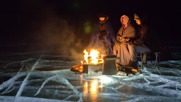Three travelers by fire right on ice at night. Campground on ice. Tent stands next to fire. Lake Baikal. Nearby there is car. People are warming around campfire and are dressed in sleeping bags.