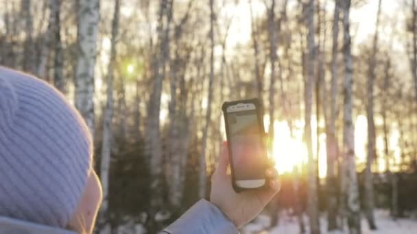 Woman is walking in the woods. Traveler is photographed on the phone in forest. Girl does selfie and communicates with her smartphone. Evening time with beautiful juicy sunset.