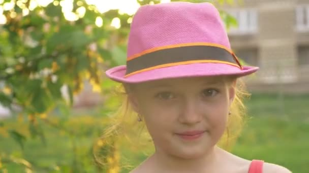 Dítě v klobouku olizuje zmrzlina. Dívka je zmrzlina vynikající krém. Zmrzlina vícebarevné na tyčce s jahodovou příchutí je oblíbená letní jídlo dětí