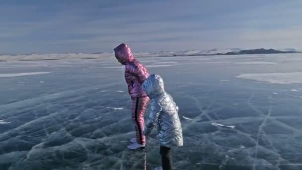 Rodina je bruslení na den. Holky jezdit postava brusle v přírodě. Matka a dcera na koni společně na ledě v praskliny. Zimní venkovní zábava pro sportovce pěkné zimní počasí.