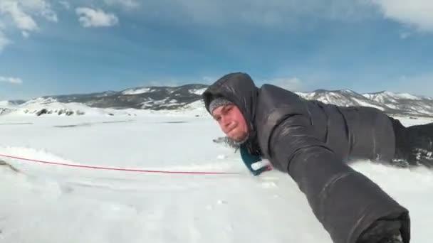 A rendkívüli ember legördül a havas jég a jég hajón. A jég-hajó az autó egy kötél van kötve. Hó repül az arcába. Orosz őrült jó.