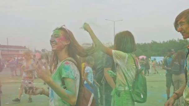 RUSSIA, IRKUTSK - JUNE 27, 2018: Happy young people dancing and celebrating during Holi Festival Of Colors. Crowd of people colored powder and having fun in arena.
