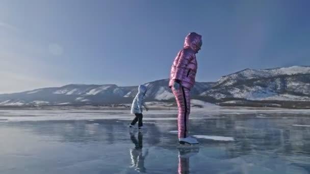 Rodina je bruslení na den. Holky jezdit postava brusle v přírodě. Matka a dcera na koni společně na ledě v praskliny. Zimní venkovní zábava pro sportovce pěkné zimní počasí