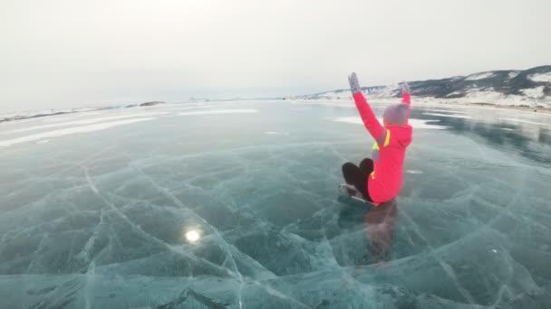 Mädchen trainiert Yoga im Winter. Frau macht Stretching und Meditation auf Eis in der Natur. Sportler übt Yoga auf schönem Eis mit Rissen. Frau macht Sport Fitness im Freien.