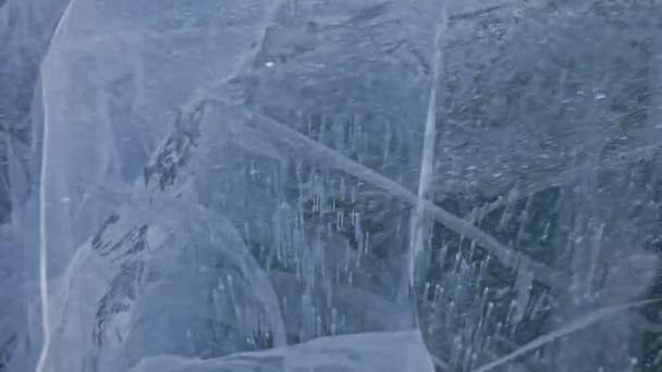 Schnee fliegt über die Eisfläche. Schneeflocken fliegen auf dem Eis des Baikalsees. Eis ist sehr schön mit ungewöhnlichen, einzigartigen Rissen. Schnee glitzert und leuchtet in Rot. Bild bei Sonnenuntergang. hoher Kontrast.