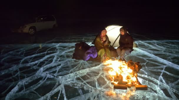 Čtyři cestovatelé ohněm přímo na ledě v noci. Tábořiště na ledě. Stan stojí vedle k ohni. Lidé jsou oteplování kolem táborového ohně. Fotograf v výhonky na fotoaparát stativ.