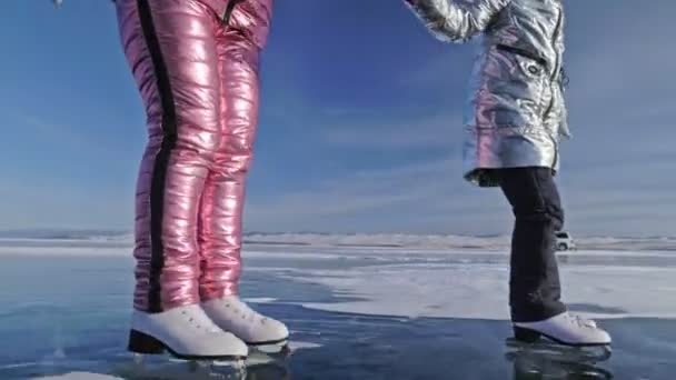 Family is ice skating at day. Girls to ride figure ice skates in nature. Mother and daughter riding together on ice in cracks. Outdoor winter fun for athlete nice winter weather. People on ice skates