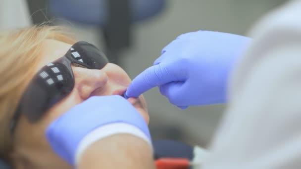 Zahnarzt behandelt Patienten in modernen Zahnarztpraxis. Kieferorthopäde arbeitet mit einem Assistenten. Im Betrieb wird Kofferdamm verwendet. Der Kunde ist Prothese machen. Arzt und Assistent arbeiten in Schutzmasken.