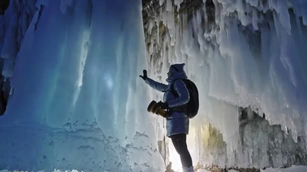 Travel woman on ice cave of Lake Baikal. Trip to winter island. Girl backpacker is walking of ice grot. Traveler looks at beautiful ice grotto. Hiker wears silver jacket, backpack, led lamp.