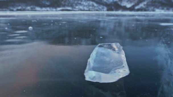 Ledová kra se otočí na ledě na pozadí úžasné horské krajiny. Zpomalený pohyb. Kamera se pohybuje za LED. LED je velmi krásně točí na ledě s magickou praskliny.