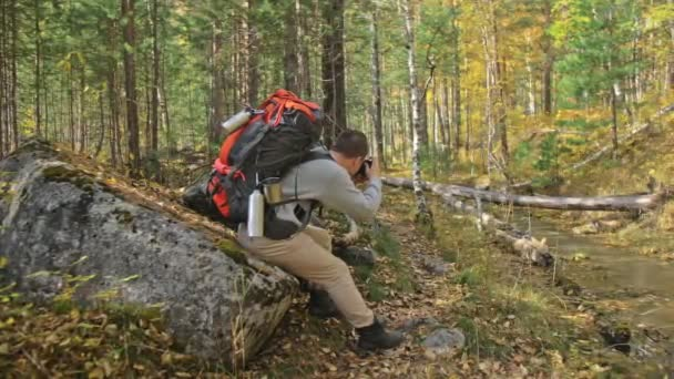 Traveler photographing scenic views in forest by mountain river. Man shooting picturesque views. Guy takes photo and video on old retro camera on film. Professional photographer traveler.