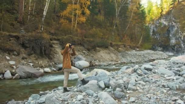 Viaggiatore fotografare panorami nella foresta di fiume della montagna. Uomo che spara una vista pittoresca. Il ragazzo prende foto e dei video sulla fotocamera dslr. Viaggiatore di fotografo professionista