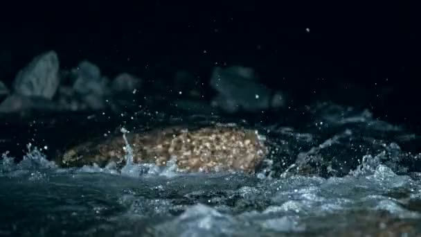 Slow motion of waves on dark water. Amazing dramatic natural background. Shooting with 180fps. Epic mystical and magic night view. Crystal clear water splashes drops and streams.
