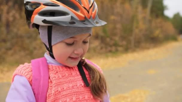 Dítě pít vodu z hliníku baňky. Jeden bělošský děti jezdí na kole silnice v podzimním parku. Malá holčička jezdecké černá oranžová mtb cyklu v lese. Biker pohybu jezdit s batohem a helmu