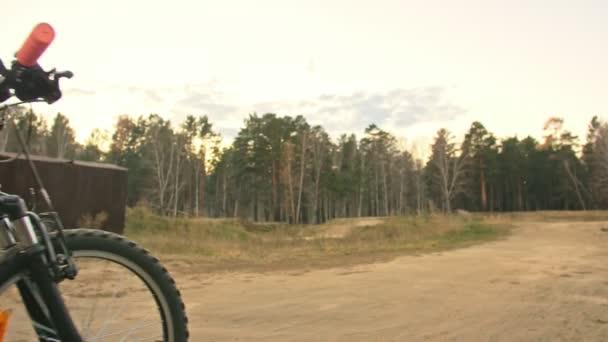 Jeden bělošský děti jezdí na kole silniční trati v dirt parku. Dívka na koni černý oranžový cyklu v dráze. Chlapče jde cyklistické sporty. Biker pohybu jezdit s batohem a helmu. Horské kolo tvrdý ocas.