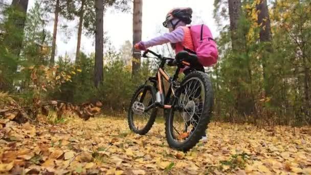 Jeden bělošský děti chodit s kolo v podzimním parku. Malá holčička vycházkové černé oranžové cyklu v lese. Chlapče jde cyklistické sporty. Biker pohybu jezdit s batohem a helmu. Horské kolo tvrdý ocas